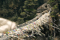 Thousands of prayer flags flutter in the breeze on the Larja Bridge in Nepal. The narrow metal swinging bridge spans the Dhud Kosi River and marks the begging of the long climb up to the Sherpa town of Namche Bazaar.