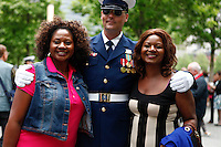 New York, USA. 22nd May, 2014. Tourist pose for a picture next to a Members of U.S. Coast Guard Silent Drill Team at the national 9-11 memorial during the Fleet Week in New York.  Kena Betancur/VIEWpress