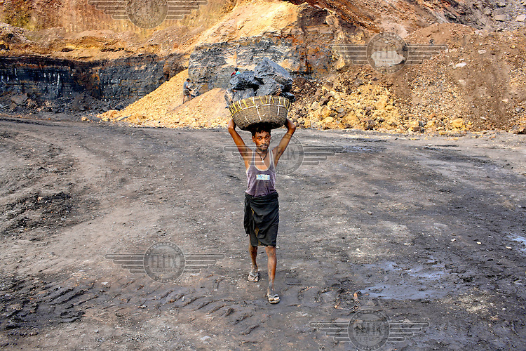 A man illegally scavenging coal carries, on his head, a basket full of big blocks of the rock that he has taken from an open-cast mine near the village of Bokapahari where a community of coal scavengers live and work. /Felix Features
