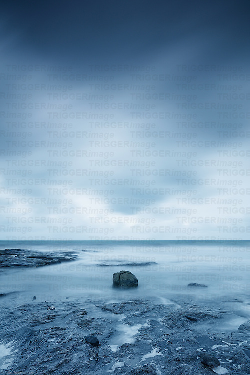 Storm over the sea with rocks in the foreground