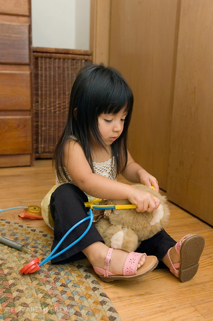 Berkeley CA Girl, age two and a half, Guatemalan, playing doctor with stuffed animal MR