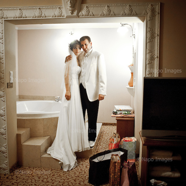 WARSAW, POLAND, NOVEMBER 2011:.Newlyweds Anna Bogatek and Andrzej Platek at their room in Venecia Palace Hotel. It was built in 2008 by Polish businessman Waclaw Gozlinski, who concluded that clients, often watching American class B movies and soap operas, are now seeking for fancy, often kitchy interiors for their parties and gatherings..As Poles are getting richer, this place is now the most popular wedding party spot in Poland, which now needs to be booked over a year in advance..(Photo by Piotr Malecki / Napo Images)..Warszawa, Listopad 2011:.Mloda para Anna Bogatek i Andrzej Platek w pokoju w hotelu Venecia Palace. Zbudowal go w 2008 roku biznesmen Waclaw Gozlinski, gdy zauwazyl, ze Polacy coraz czesciej preferuja kiczowate wesela w ociekajacych sztukateria wnetrzach jak w Las Vegas lub telewizyjnych operach mydlanych. Hotel jest ogromnym sukcesem, czesto trzeba go rezerwowac z ponad rocznym wyprzedzeniem..Fot: Piotr Malecki / Napo Images