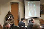 Sniper suspect John Allen Muhammad, left seated, listens to a witness as a photo of sniper victim Conrad Johnson is displayed on a screen in courtroom 10 at the Virginia Beach Circuit Court in Virginia Beach, Virginia on November 3, 2003.<br /> Credit: Lawrence Jackson - Pool via CNP