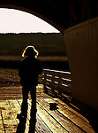 A woman stands inside an old covered bridge.