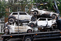 A lorry removes burnt out cars in the London borough of Hackney. London saw the beginnings of riots on Saturday evening, after a peaceful protest in response to the shooting by police of Mark Duggan during an attempted arrest, escalated into violence. By the third night of violence, rioting had spread to many areas of the capital and to other cities around the country.