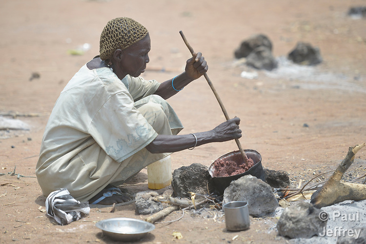 Edith Ayok cooks beans that she received from the ACT Alliance on April 7, 2017, in Rumading, a village in South Sudan's Lol State where more than 5,000 people, displaced from their homes by drought and conflict, remain in limbo. In early 2017, they set out walking for Sudan, seeking better conditions, but were stopped from crossing the border. They remained camped out under the trees at Rumading, eating wild leaves as the rainy season approached.<br /> <br /> In early April, Norwegian Church Aid, a member of the ACT Alliance, began drilling a well in the informal settlement and distributed sorghum, beans and cooking oil to the most vulnerable families. The ACT Alliance is carrying out the emergency assistance in coordination with government officials and the local Catholic parish.