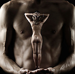 Beautiful naked woman standing on hands of a muscular man