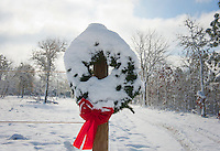 Christmas wreath covered in snow hanging on a fence pole