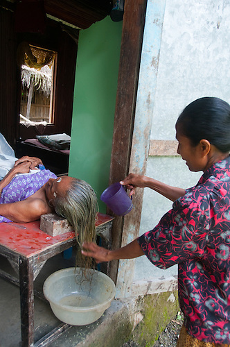 Java, Elderly woman is treated for high blood pressure and headaches through a traditional medical practice of washing her hair with coconut milk.