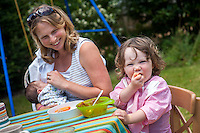 A young mother breastfeeds her new baby whilst feeding her toddler with a spoon at the same time at a table in the garden on a summer's day.<br /> <br /> 26/08/12<br /> Hampshire, England, UK