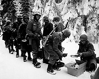 Chow is served to American Infantrymen on their way to La Roche, Belgium.  347th Inf. Regt. January 13, 1945.  Newhouse.  (Army)  <br /> FILE #:  111-SC-198849<br /> WAR &amp; CONFLICT BOOK #:  1075