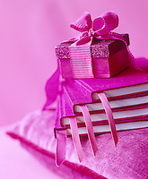 Detail of a pink present on a pile of pink notebooks