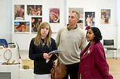 "A current student showing a father & daughter around the exhibition, ""Heart of Brazil"" by Sue Cunninham.  Open Day at Kingston College when prospective students visit."