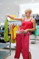 Woman looking and comparing different clothes in shop. Fashion, retail store, shopping.
