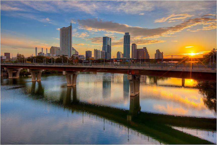 Taken from the Lamar Bridge, this image shows the sun rising over downtown Austin and the Austin skyline with the Frost Tower in the distance and Lady Bird Lake in the foreground.