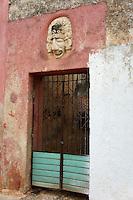 Pre-Columbian mask replica over a metal gate in Santa Elena, Yucatan, Mexico..