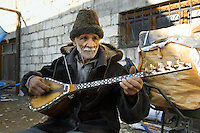"Azerbaijan. Ganja region. Ganja. An old caucasian man with a hat and a white beard plays the ""saz"", a plucked string instruments, popular in Azerbaijan, The saz is a long-necked lute of folk traditions and is descended from the kopuz; a generic name for several forms of stringed instrument used in Azeri music.  © 2007 Didier Ruef"