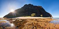 The sun crests the cliffs of Miloli'i beach on the rugged Na Pali coast of Kauai.