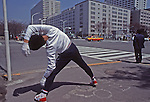 On the sidewalk at a street intersection in Tokyo a youth does yoga or tai chi