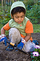 A young gardener learns how to use a garden trowel.