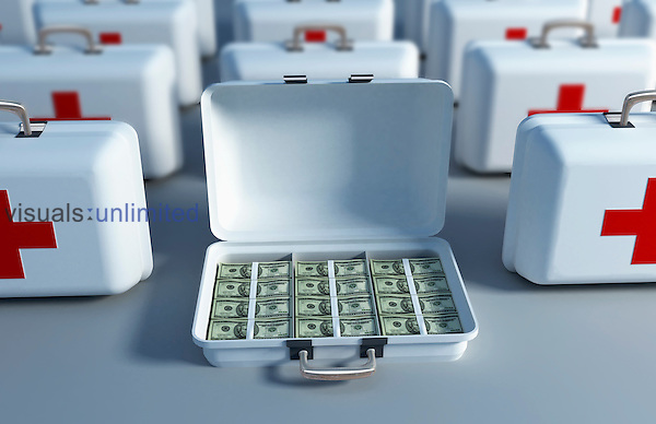 An image of rows of first aid boxes, one of which is opened and filled with cash. Royalty Free