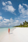 Baresdhoo Island, Laamu Atoll, Maldives; a woman in a red bikini on a deserted, white sand beach in the Maldives on a beautiful sunny afternoon with blue skies and puffy white clouds