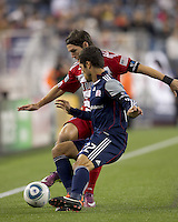 FC Dallas defender Zach Loyd (91) attempts to control the ball as New England Revolution midfielder Benny Feilhaber (22) defends. In a Major League Soccer (MLS) match, the New England Revolution defeated FC Dallas, 2-0, at Gillette Stadium on September 10, 2011.