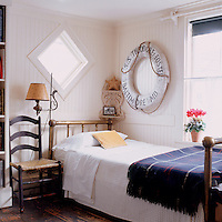 The small guest bedroom has a nautical theme with an antique life preserver decorating the wall next to the bed