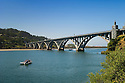 Fishermen in boat and jetboat tour coming under Rogue River Bridge; Gold Beach, Oregon Coast.