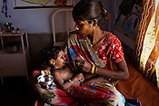 24 year old Jaikunwar feeds her malnutritioned 15 month old daughter, Anjana at the 'Nutritional Reahabilitation Centre' at the pediatrics section of Community Health Centre (Block Hospital) in Talbehat, Uttar Pradesh, India. The Indian government spends $1.4 billion a year - on programs that include weighing newborn babies, counseling mothers on healthy eating and supplementing meals, but none of this is yeilding results. According to UNICEF, some 48% of Indian children, or 61 million kids, remain malnourished, the clinical condition of being so undernourished that their physical and mental growth are stunted. Photo: Sanjit Das/Panos for The Wall Street Journal.Slug: IMALNUT