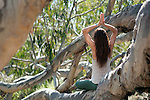 Reverent woman meditating on a giant tree.
