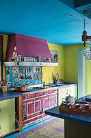 The turquoise and yellow painted kitchen features a pink oven and matching extractor
