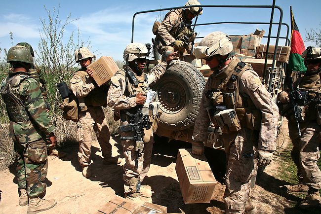 U.S. Marines from Company L, 3rd Battalion, 6th Marine Regiment load up on boxes of food and water that have been delivered to them during a three-day mission near Marjah, Afghanistan. March 11, 2010. DREW BROWN/STARS AND STRIPES