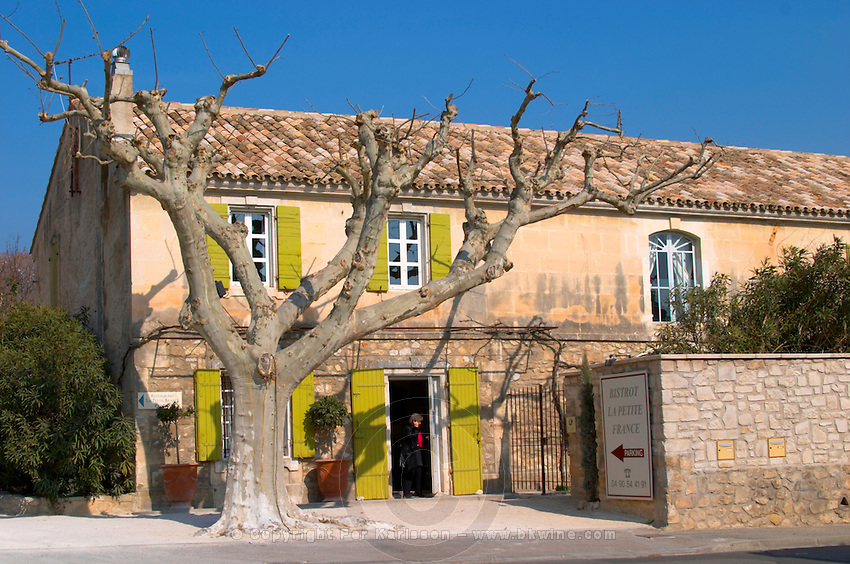 The restaurant Bistrot La Petite France in Le Paradou with a naked tree and a person on a mobile phone in the door, Provence, Bouches du Rhone, France