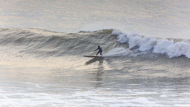 Longboarder surfing at Freshwater Bay, Isle of Wight