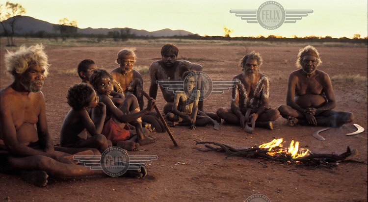 Aborigines sit by a fire after sunset in the desert of Central Australia.