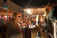 Group of friends having drinks at an outdoor rooftop party on 6th Street in downtown Austin, Texas.