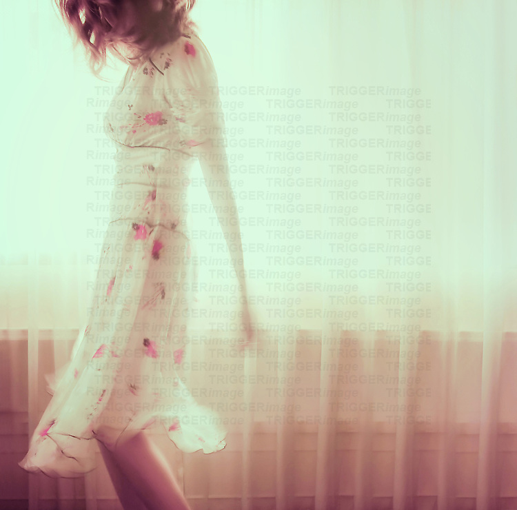 Young woman wearing a delicate summer floral dress walking in front of a window with natural sunlight