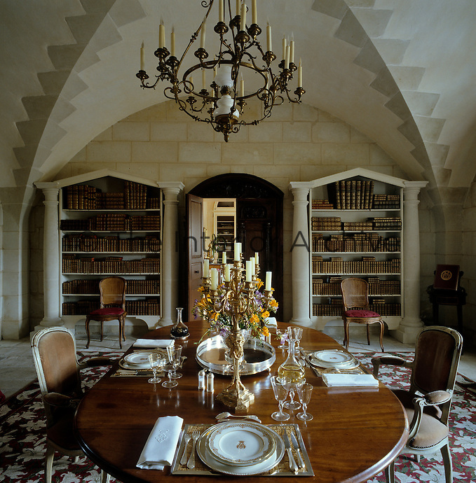A pair of classically inspired book cases stand on either side of the entrance to this dining room which features a vaulted ceiling