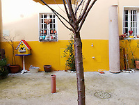 Switzerland. Canton Ticino. Agra. A private house with a yellow wall and two windows with bars and hearts. A small house for the birds, a plastic pipe and a tree's trunck. Agra is 10 km distant from Lugano. 22.1.2012 © 2012 Didier Ruef..