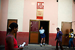 A security guard stands in the doorway of a government building in Barrio Chino, in Havana, Cuba, on Saturday, April 26, 2008. The Chinese immigrants who remain in Cuba didn't have enough money to leave the island at the beginning of the Cuban revolution..
