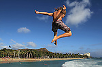 A man jumps off the Waikiki Beach wall with Diamond Head in the background, Honolulu, HI.