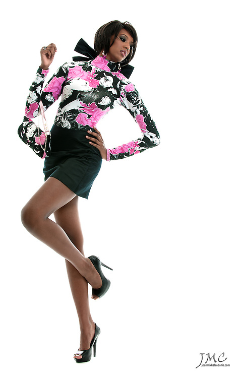 Beautiful fashion model with long legs, in black skirt and heels, pink and white blouse