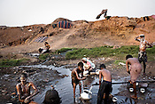 After a long days' work, miners gather to wash themselves in village Bokapahari in Jharia, Jharkhand, India. miners work for 9-10 hours a day and make Rs.150 ($3.5) a day loading the coal trucks in the BCCL coal mines in Jharia. Coal fires rage just below the surface of the ground, making it too hot to walk with naked feet, noxious gases spew up from fissures, making the environment toxic. Photo: Sanjit Das