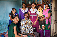(Clockwise from left) Niru, 24, and her sisters, Daksha 15, Kailash, 19, Mukta, 22, and Nayna 27 carrying her son Dev 3, and their father Jethabhai Rathod, 60 pose for a family Portrait at home in Surendranagar, Gujarat, India on 14 December 2012. Niru, the 8th child in a family of 11 girls born to Jethabhai, a Dalit construction worker, has been using videography for social change since 2006. She shoots and produces her own short documentaries and is a committed video activist, having conducted hundreds of village video screenings where she also speaks to thousands of men, shattering their ideas about what a woman and a Dalit can do while bringing massive changes to the communities she documents. Photo by Suzanne Lee / Marie Claire France
