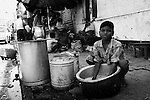 A boy ashes rice on the side of the street in Calcutta/Kolkata, India