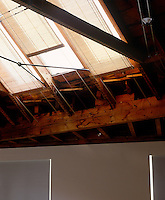 The massive wooden beams have been left exposed in the living room of a restored mews house where daylight comes from skylights shaded by a series of blinds