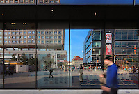 Reflections in the window of the U-Bahn or underground train station in Alexanderplatz, Berlin, Germany. Reflected are the Berolinahaus, people and shops. Picture by Manuel Cohen