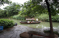 Tourists travel by boat through the Xixi wetlands which lie in the west of the city of Hangzhou. This is China's 'first national wetland park,' dubbed as such to act as a role model to all other wetlands in China and to supposedly show how to effectively manage and restore wetlands, notably urban wetlands. Zhejiang Province. China. 2010