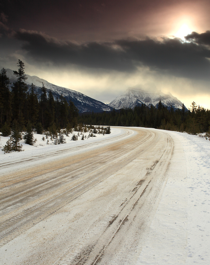 The heavy snow diffuses the sunlight along a snow-covered Highway 16 in Jasper National Park, Alberta, Canada.